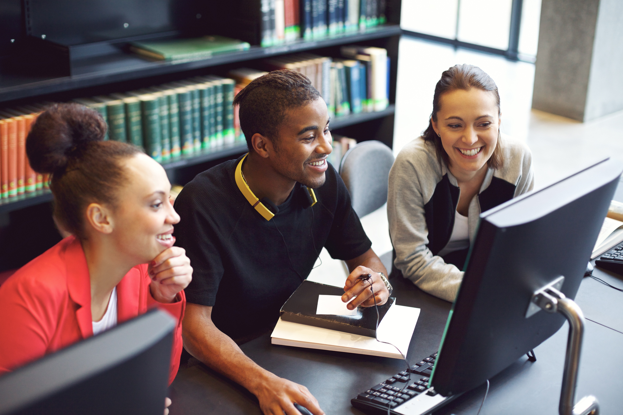 Students Working On Computer In A College Library - GED